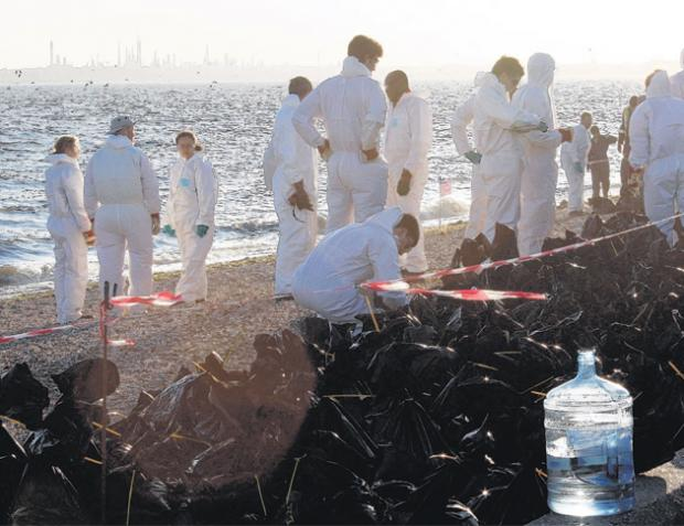 Fawley workers on the beach at Hill Head remove bags of shingle contaminated with oil.