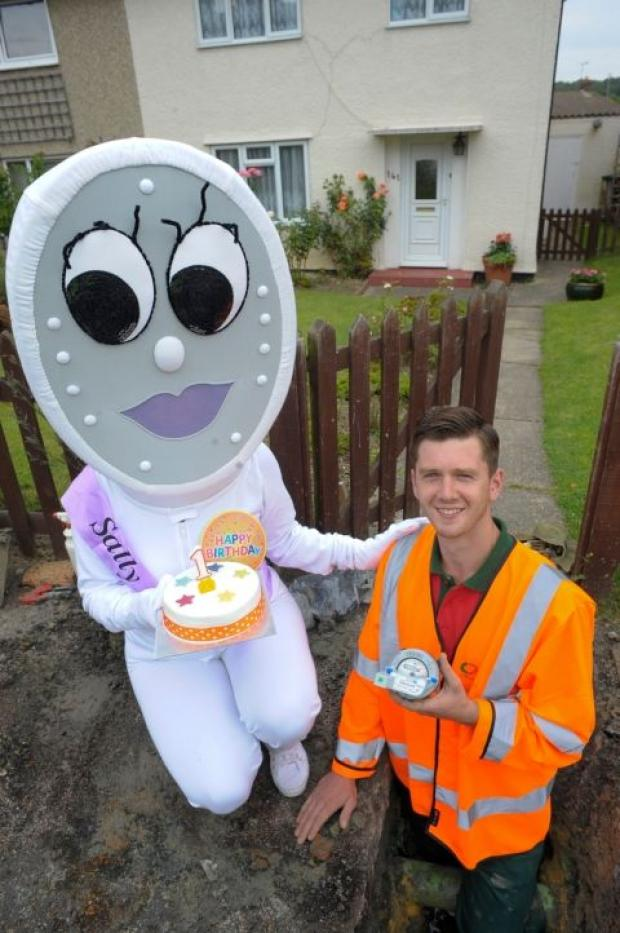 Installation team member Jack Connor with South East Water's mascot Sally Shower